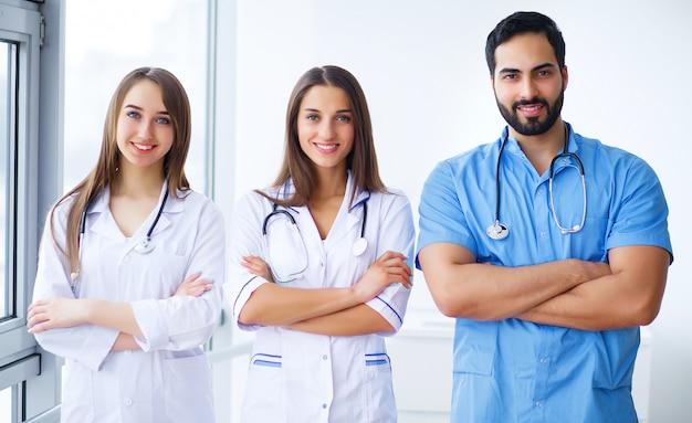 医師の成功チームはカメラを見て、病院に立っている間笑顔 Premium写真
