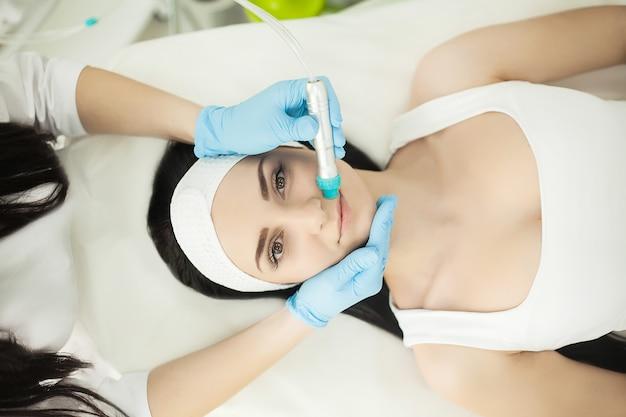 現在の治療法を使用して皮膚療法を楽しんでいる美容スパで横になっている女の子 Premium写真