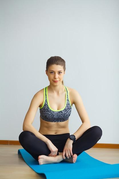 若いヨギ魅力的な女性のヨガの概念の練習、スポーツウェア、黒のタンクトップとズボン、フルの長さを着て Premium写真