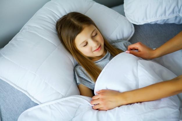 かわいい女の子は自宅でベッドで寝ています、お母さんは羽毛布団で彼女を覆っています。 Premium写真