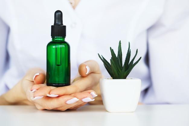 漢方薬科学者、皮膚科医は研究室で有機天然ハーブ化粧品を作る。美容健康的なスキンケアコンセプト。クリーム、血清。 Premium写真
