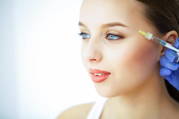 美容とケア美しい顔を持つ若い女性の肖像画。美容師が注射をします。高解像度 Premium写真