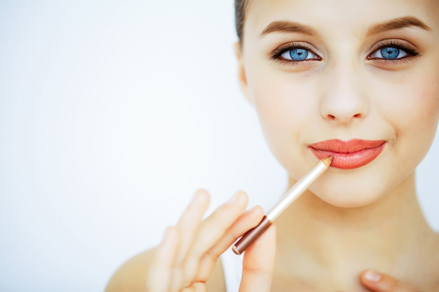美容とケア美しい肌を持つ若い女性の肖像画。美しい唇。彼女の手で口紅を持つ女の子。美しい青い目を持つ女性。化粧。唇のケア Premium写真