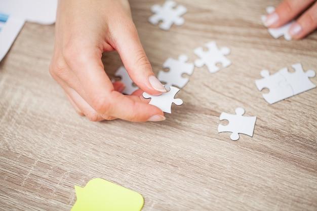ビジネスコンセプト、女性の手が会社の成功を象徴するパズルを作る Premium写真