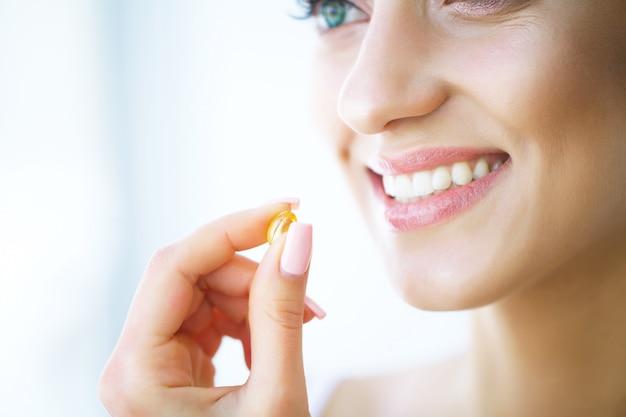 美しい女性は薬、薬を服用します。ビタミンとサプリメント Premium写真