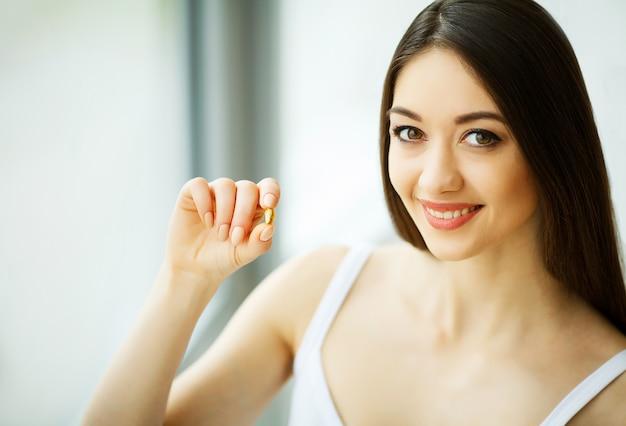 美しい女性が薬を飲んでビタミンとサプリメント Premium写真