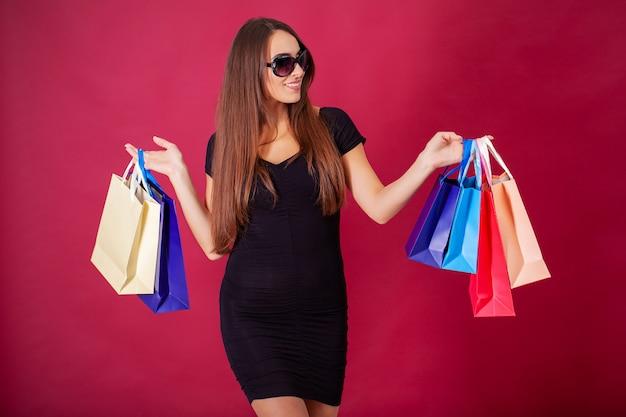 買い物の後バッグとスタイリッシュな黒の服を着てかなり若い女性 Premium写真
