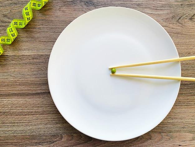 白い皿の上の画像のエンドウ豆のトリミング、フォークと測定 Premium写真