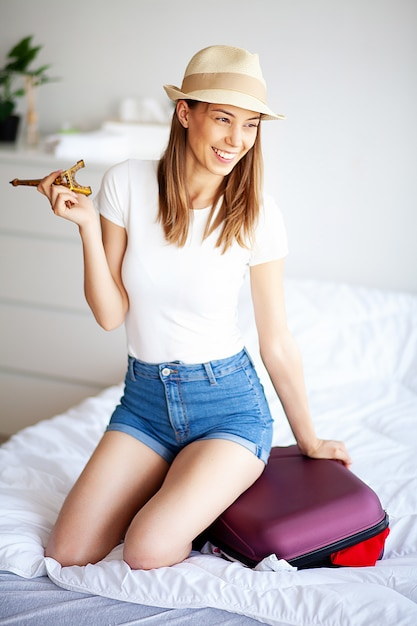 女性の足が手荷物、自宅で若い女性がベッドに敷設を引き上げた。白い寝室 Premium写真