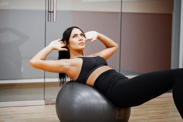 フィットネスガールセクシーな運動女の子はジムでワークアウト。運動をしているフィットネス女性 Premium写真