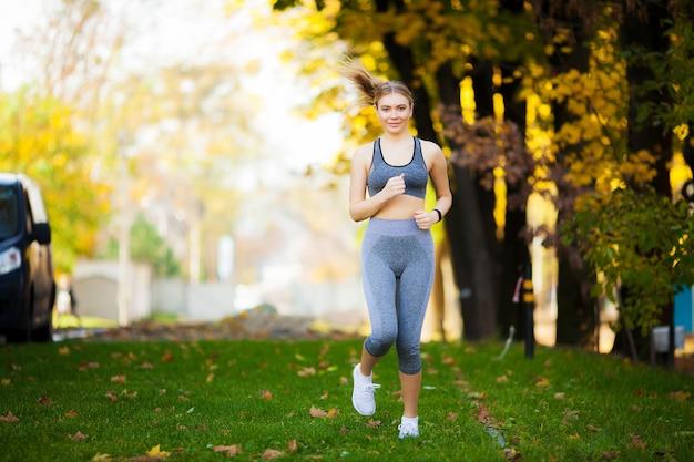 フィットネス、美しい若い女性は公園でのエクササイズ Premium写真