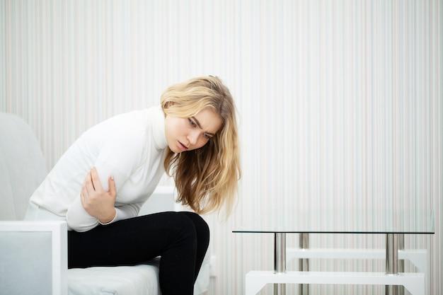 ソファーに座っていた胃の痛みで疲れた女性 Premium写真