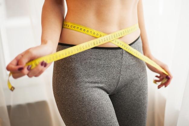Руки измеряют талию скотчем. стройная и здоровая женщина у себя дома Premium Фотографии