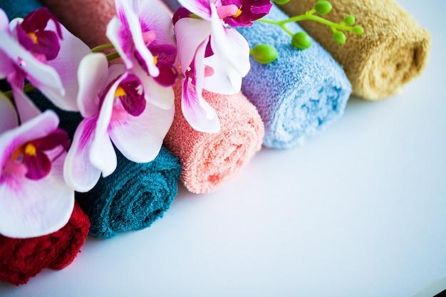 色付きのタオルとバスルームの白いテーブルの上の蘭。 Premium写真