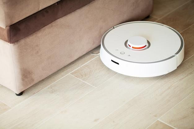 Умный дом. пылесос-робот работает на деревянном полу в гостиной. Premium Фотографии