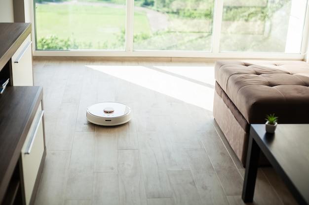 スマートハウス掃除機ロボットは居間の木の床の上を走ります。 Premium写真