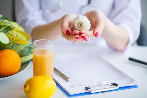 Рацион питания. доктор диетолог держит чеснок в своем кабинете. Premium Фотографии