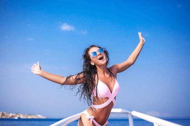 豪華な白いヨットの上で白い水着でセクシーなブルネットの少女。 Premium写真