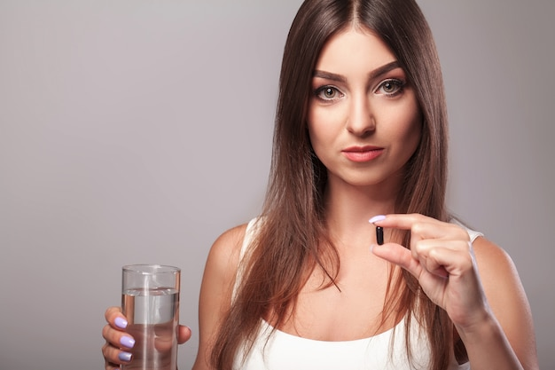 風邪やインフルエンザ。水のガラスを保持しているとカプセルを取っている女性 Premium写真