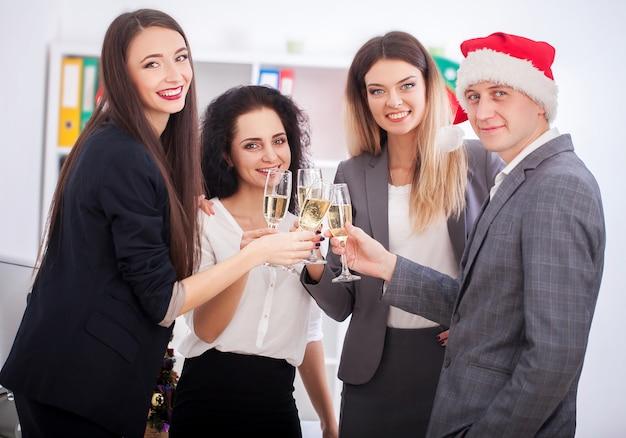Счастливые деловые люди в шляпах санта смотрят на камеру и улыбаются во время празднования нового года Premium Фотографии