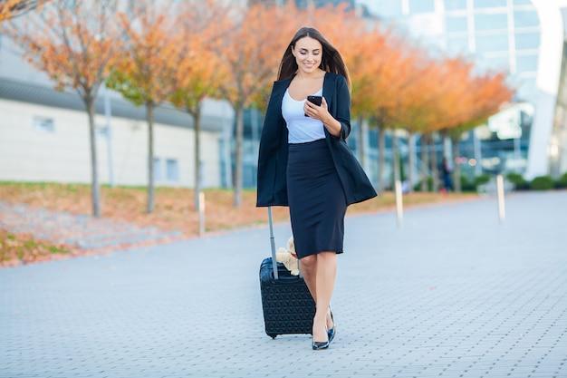 スーツケースを持つ若い陽気な女性。旅行、仕事、ライフスタイルの概念 Premium写真
