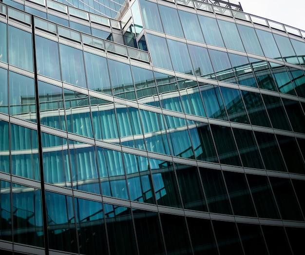 青い曇り空の上の現代ガラス建築高層ビルの織り目加工の背景に視点と下側の角度のビュー Premium写真