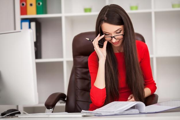 座っていると何かを書くの赤いドレスを着たビジネス女性の笑みを浮かべてください。 Premium写真