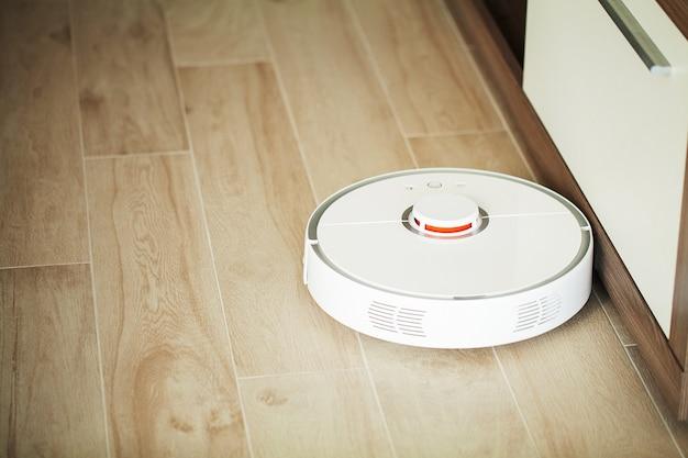 スマートハウス、掃除機ロボットは居間の木の床の上を走ります、 Premium写真