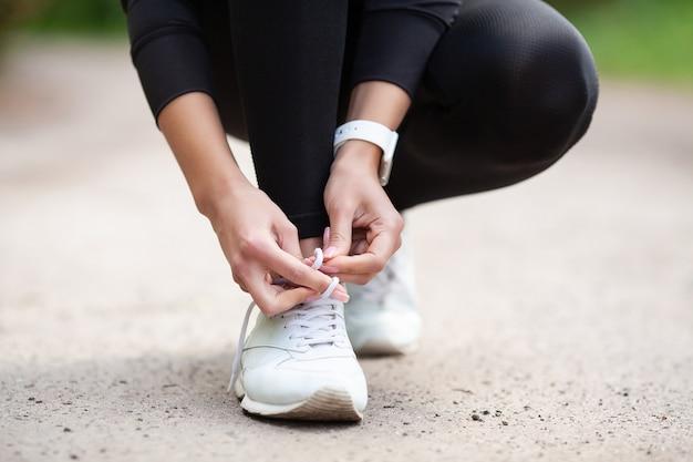 スニーカーの問題、ジョギングの準備をしている彼女の靴を結ぶ女性ランナー Premium写真