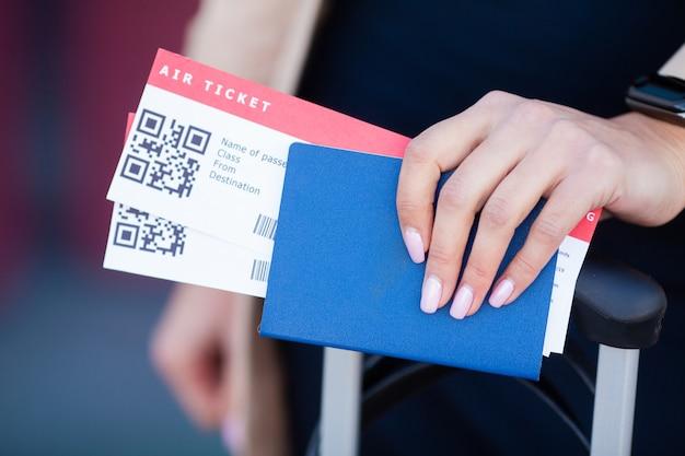 Путешествовать. крупным планом девушки с паспортами и посадочный талон в аэропорту Premium Фотографии