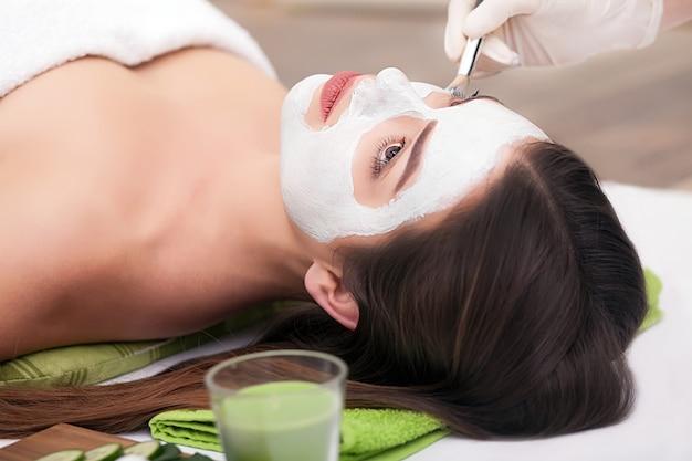 スパサロンで女性の顔に栄養マスクを適用する手 Premium写真