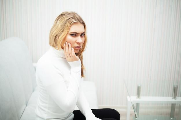 疼痛。歯の問題。女性は歯に痛みを感じます。彼女の歯の激しい痛みに苦しんでいる美しい、悲しい少女の写真。魅力的な女性は痛みを伴う歯痛を感じる Premium写真
