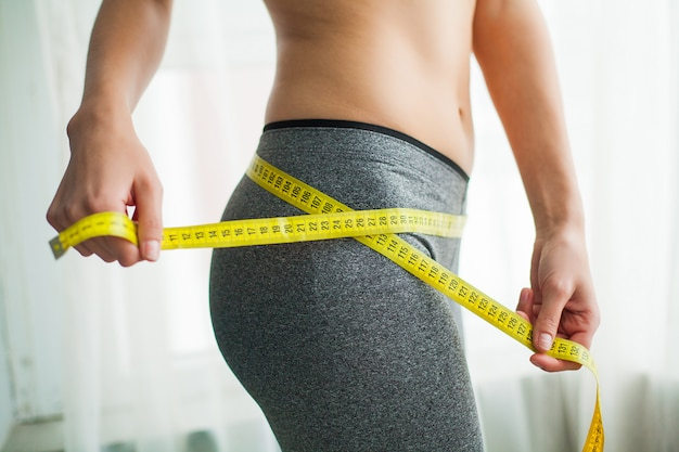 テープで腰を測定する手。彼女の家でスリムで健康な女性 Premium写真