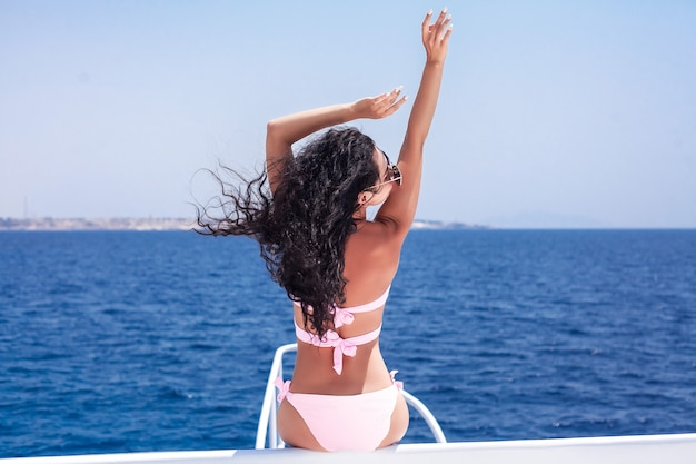 若い女性が船の甲板から海を賞賛します。海のクルーズ、旅行と休暇、世界一周旅行 Premium写真