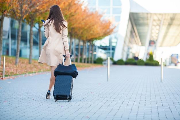 若いカジュアルな女性は飛行機で待っているスーツケースとウィンドウで空港に行きます Premium写真