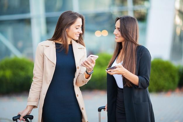 Изображение двух радостных европейских женщин, глядя на смартфон, стоя с багажом возле аэропорта в ожидании рейса или после вылета. воздушное путешествие Premium Фотографии
