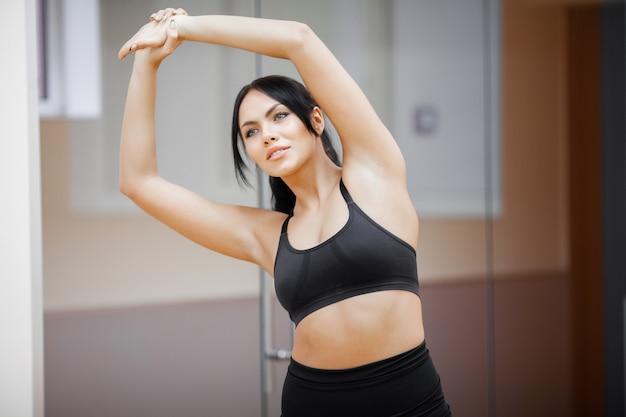 フィットネス女の子。ジムでワークアウトセクシーな運動少女。運動を行うフィットネス女性 Premium写真