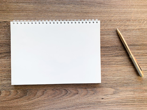 木製テーブルの上の白いノートトップビュー Premium写真