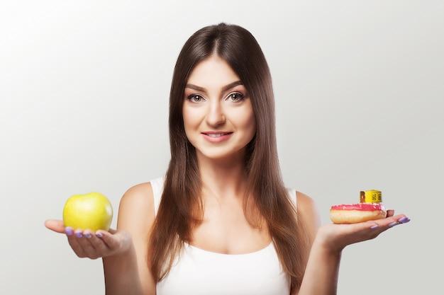 健康食品。女性は体重を減らしています。若い女の子は食べ物やスポーツを選ぶことをためらいます。 Premium写真