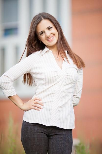 近代的なオフィスの背景に美しいビジネス女性 Premium写真