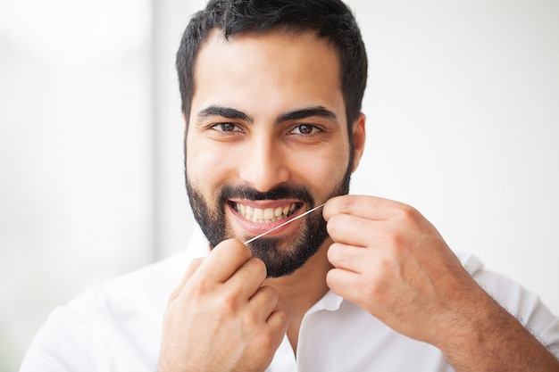 歯の健康。健康的な歯をフロス美しい笑顔を持つ男 Premium写真