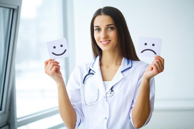 悲しいと陽気な笑顔のシンボルと紙を保持している女性の手 Premium写真