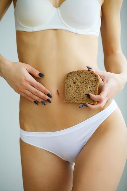 茶色のパンのスライスを押しながら胃に触れる下着を着ている女性のクローズアップ Premium写真
