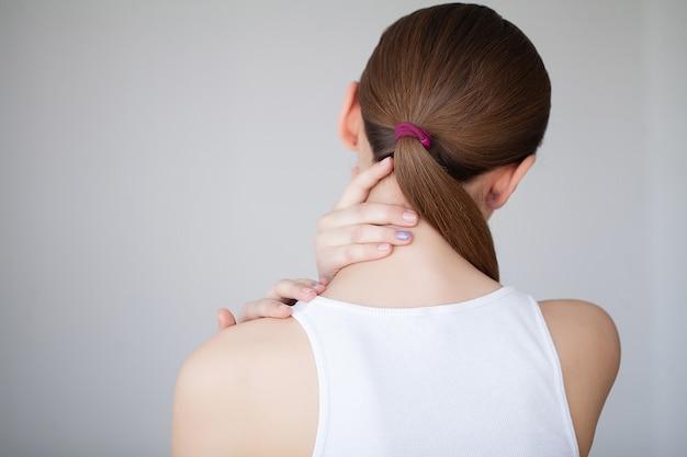首の痛み。痛みの女性。歯痛を感じる美少女 Premium写真