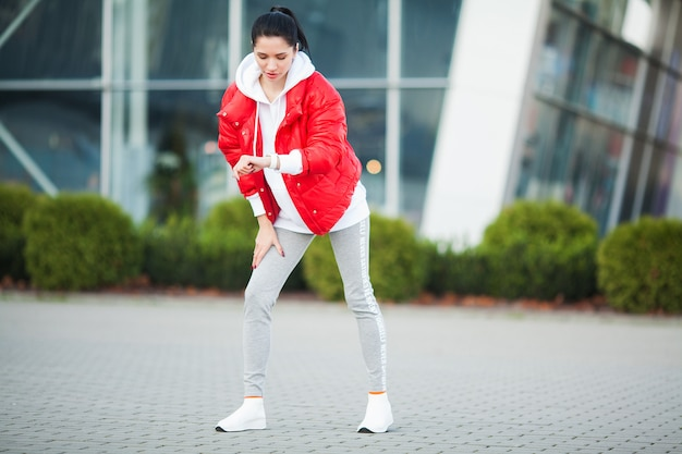 体を伸ばして、通りで運動をしている女性 Premium写真