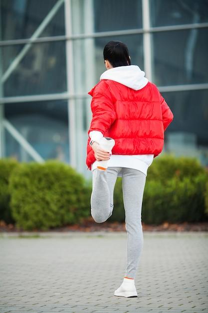 Женщина растяжения тела, делая упражнения на улице Premium Фотографии