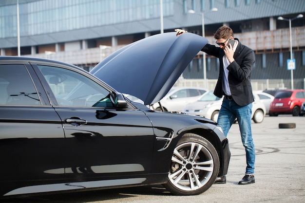 道路上の問題。スマートフォンを呼び出す壊れた車を持つ男 Premium写真