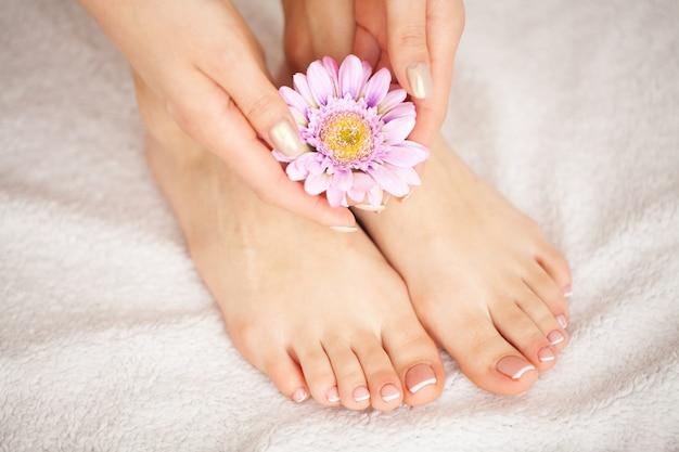 女性のフレンチペディキュア。長い脚、柔らかい肌に触れる女性の手を閉じます。脱毛 Premium写真