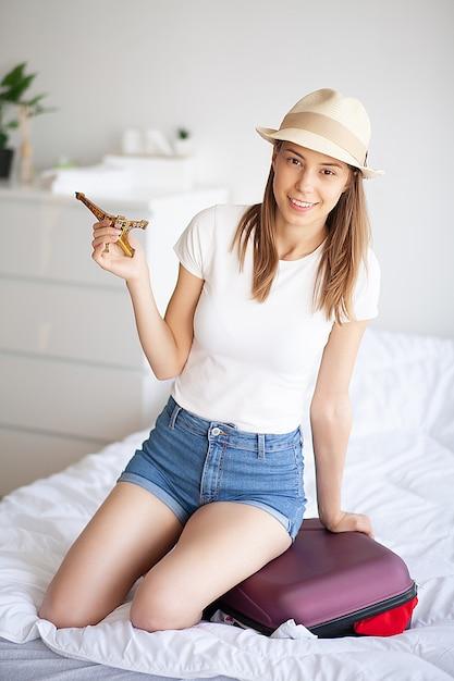 女性の足が荷物で育った、自宅の若い女性がベッドに横たわっています。白い寝室。 Premium写真