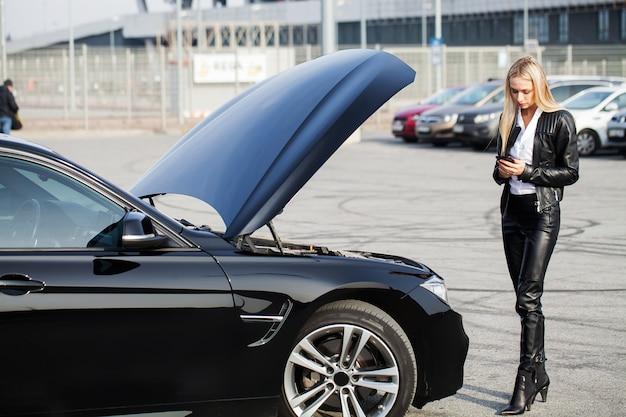 道路上の問題。スマートフォンで呼び出す壊れた車を持つ女性 Premium写真